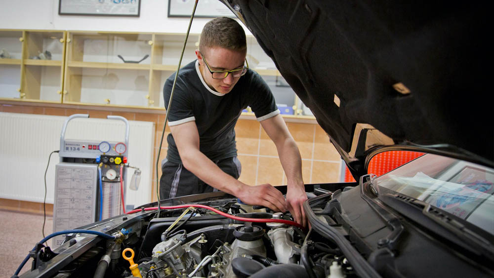 Student pracuje na motoru auta